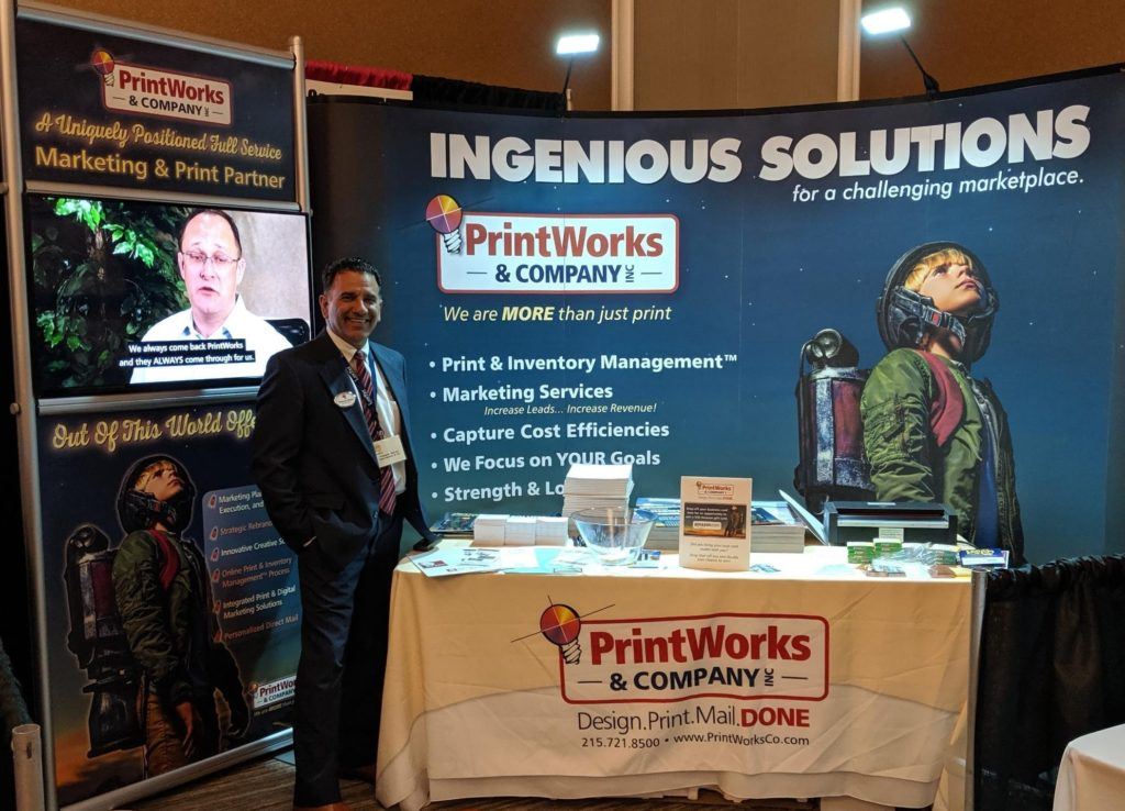 Salesman Thomas Rolon stands with new PrintWorks Digital Display at Delaware Valley Legal Expo in King of Prussia, PA
